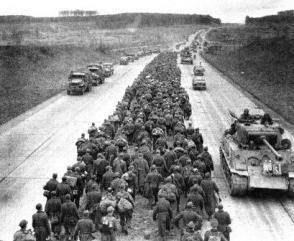 German prisoners are marched down an Autobahn near Giesen, as American Forces roll past them on their way to the front.