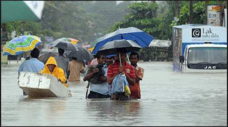 Sri Lankans wade through rain water on a flooded road of PiliyanDala suburb of Colombo on November 11, 2010